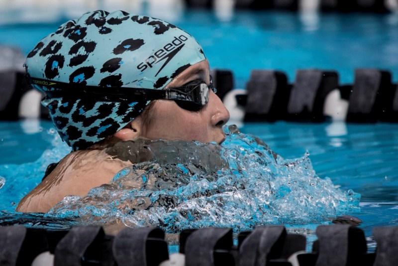 A atleta está na piscina, com os braços submersos e a cabeça erguida; ela está de óculos e com uma touca azul. ela é branca.
