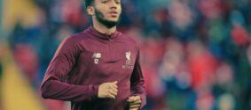 Joe Gomez correndo com a camisa vermelha do Liverpool