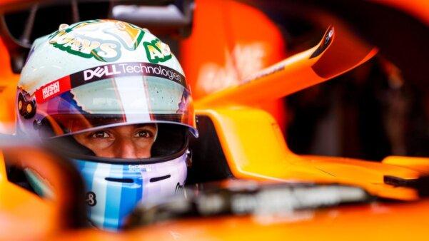 Daniel Ricciardo de capacete dentro do carro da McLaren, parado no boxes. Close. Apresenta detalhes do carro em laranja e o capacete branco com detalhes em azul