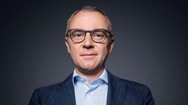 Stefano Domenicali, chefe da Fórmula 1. Homem, branco, de óculos com aro preto, camisa azul e blazer azul marinho. Imagem em plano americano, do peito para cima.