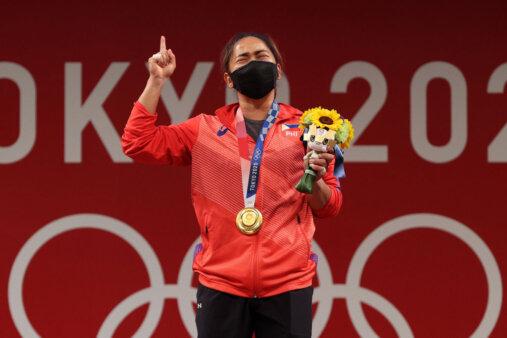 Hidiliz Diaz com a medalha e o uqyê de flores na Olimpíada de Tóquio. Verste agasalho vermelho com calça preta, m[ascara preta no rosto. Tem traços orientais.