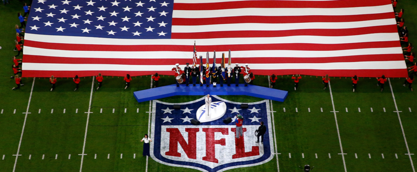 Imagem de um campo de futebol americano com o logo da NFL, uma bandeira dos Estados Unidos e um palco