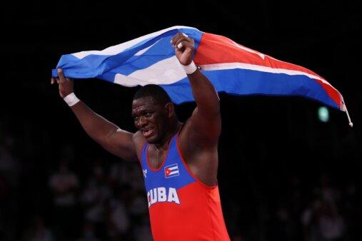 """Mijain Núñez carrega bandeira cubana depois de conquistar o tetracampeonato olímpico na luta greco-romana. É um homem negro, forte, vestindo regata vermeha e azul com o escrito """"Cuba"""" em branco."""