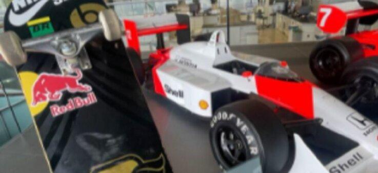 Imagem da McLaren de Senna, pintada em vermelho e branco, em segundo plano; em primeiro plano, o pedaço de um skate